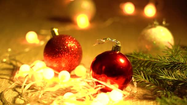 Červené, bílé kuličky, jehličnaté větve a věnce žlutých lamp leží na zblízka na stole. Vánoční svátky a vánoční příprava koncepce