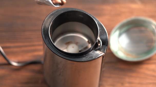 Nalijte kávová zrna do mlýnku. Makro video o tom, jak se kávová zrna nalévají na čepel elektrického mlýnku na kávu.