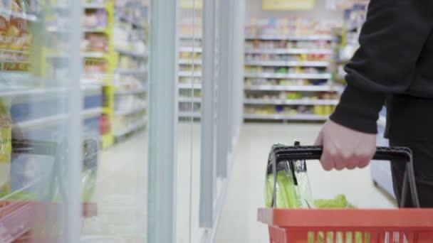 Jekaterinburg, Rusko - prosinec 2020: Vezměte si produkt z chladničky v obchodě. Muž s košíkem s potravinami v supermarketu kráčí po chladících komorách