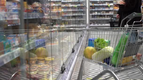 Rodina nakupuje v supermarketu. Košík s potravinami vedle chladniček