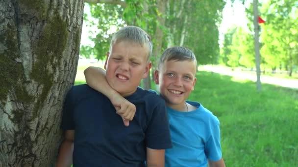 10-12 yaşlarında iki erkek çocuk, kameranın önünde sarılıp oynaşıyorlar. En iyi arkadaşlar. Mutlu bir çocukluk. Hafta sonu dışarıda.