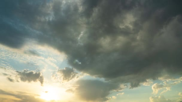 Time lapse of dramatic heavy gray clouds at sunset, illuminated by the sun. The rays and glare of the sun through the clouds