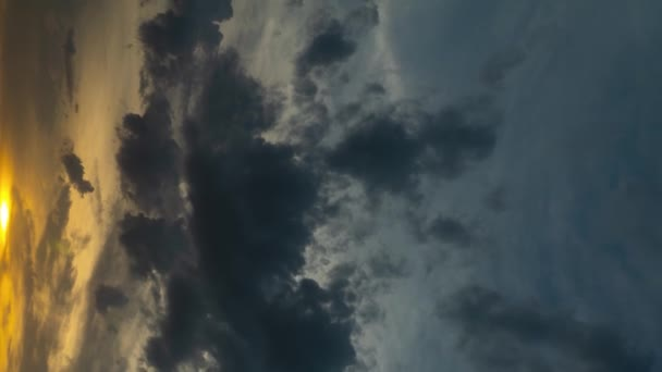 vertical format video- Time lapse of dramatic heavy gray clouds at sunset, illuminated by the sun. The rays and glare of the sun through the clouds