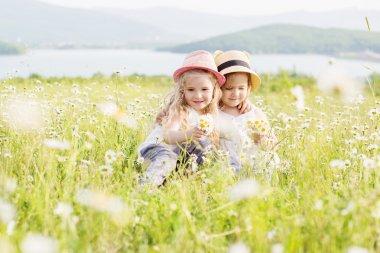Two cute little girls hugging in the field