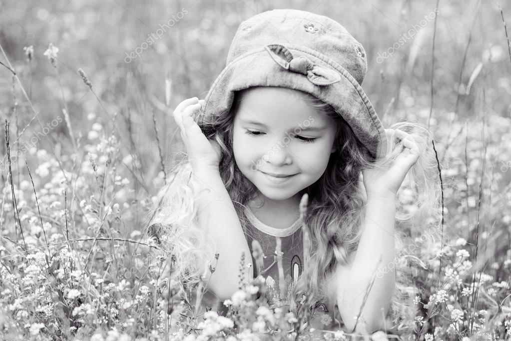 Portrait of a cute little girl on the meadow