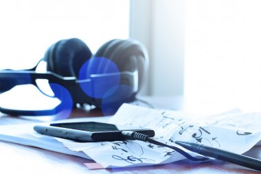 Closeup of smart phone with headphone on musical notes paper wit