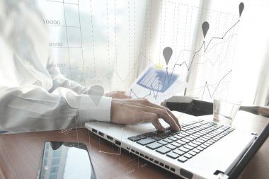 Business man hand working on laptop computer on wooden desk as c