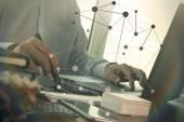 Üzletember kézi használ laptop és mozgatható telefon-val borús alap