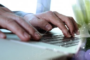 Close up of business man hand working on laptop computer with di