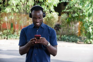 Man listens to music with headphones using a mobile phone outdoors.