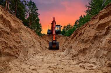 Excavator dig trench at forest area on amazing sunset background. Backgoe on earthwork for laying crude oil and natural gas pipeline or water main pipes. Construction the sewage and drainage