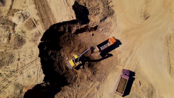 Luftaufnahme eines Baggers, der den Sand in einen Kipper verladen hat. Bagger bei Erdarbeiten. Tagebauentwicklung und Sandabbau. Baugrube für Baugrube. Erdbewegungen auf Baustelle.