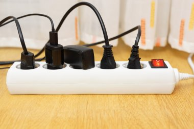 many electrical appliances pluged in surge protector. Power cons