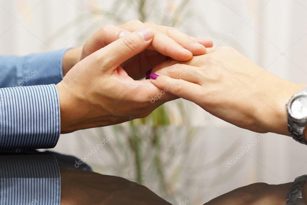 Die Hand des Mannes streichelt eine Frauenhand. Liebhaber