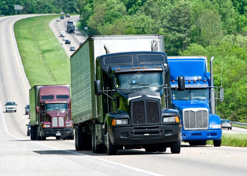 Big Trucks Moving Down A Long Highway