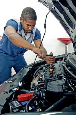 Confident Young Mechanic Checking Under Hood Of Vehicle