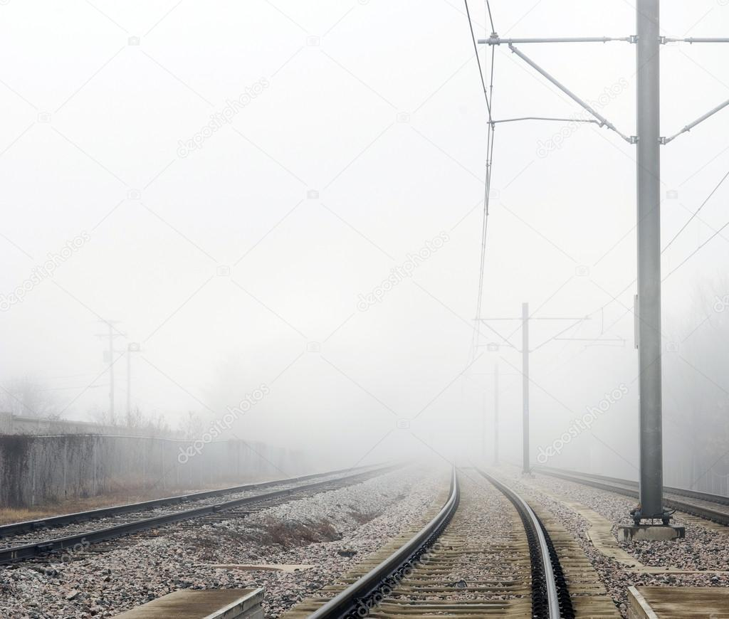 Train Tracks Disappearing Into Fog Concept