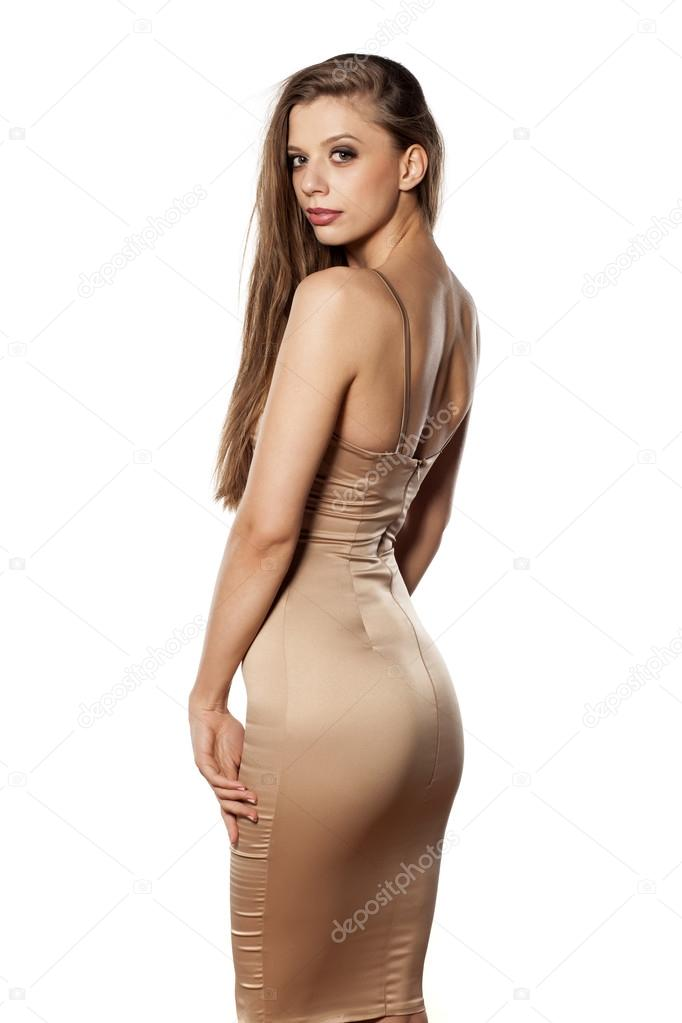 3228a3cf21f0 Γυναίκα στο στενό φόρεμα — Φωτογραφία Αρχείου · Back view of an elegant  young woman in tight dress posing on white background — Εικόνα από VGeorgiev