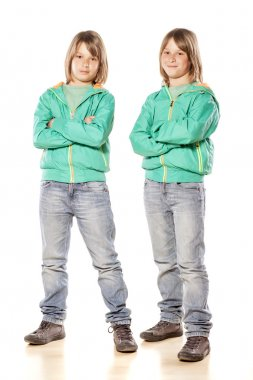 Twin brothers in green jackets and jeans posing on white background stock vector