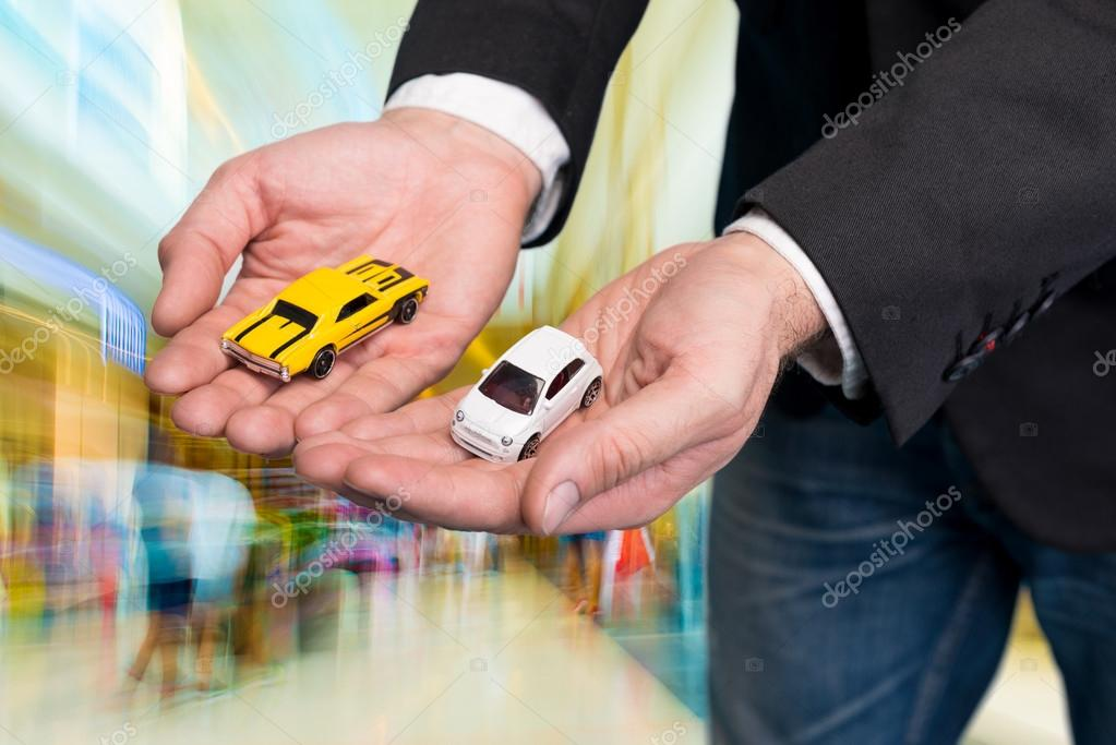 Businessman in black suit holding two small car models