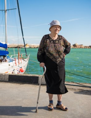Old woman standing with a cane