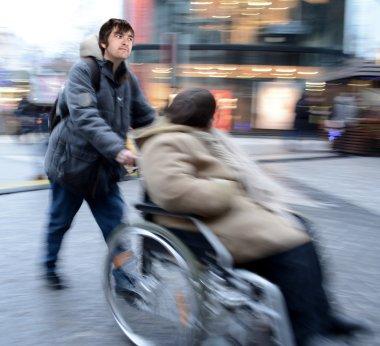 Man pushing  woman in a wheelchair