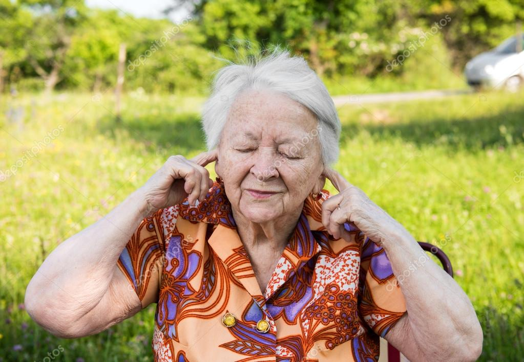 Old woman  covers her ears with  hands