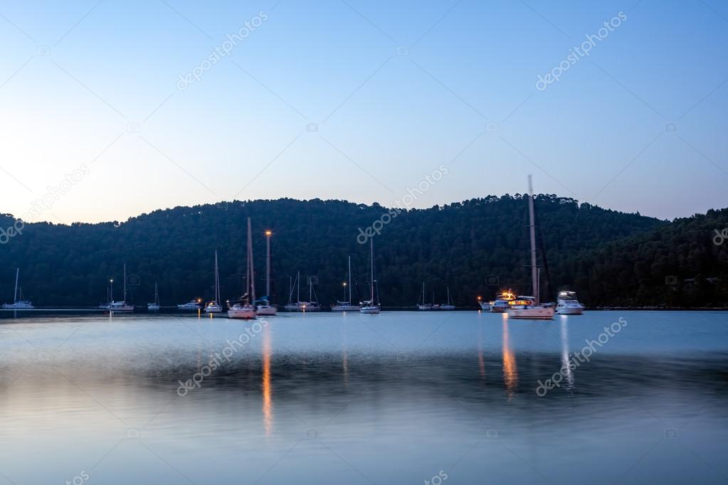 Anchored yachts and sailboats in the sunset