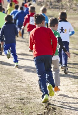 Junior athletics runner on a cross country race. Outdoor circuit