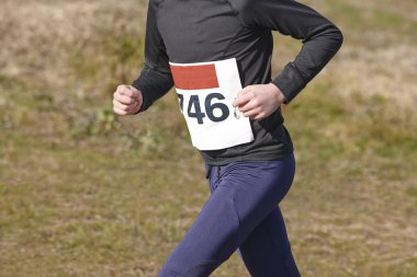 Young athletic runner on a cross country race. Outdoor circuit