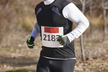 Male athletic runner on a cross country race. Outdoor circuit.