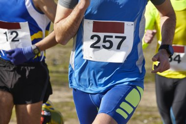 Male athletic runners on a cross country race. Outdoor circuit.