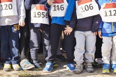 Children athletics runner on a cross country race. Start line