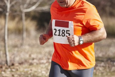Senior athletic runner on a cross country race. Outdoor circuit