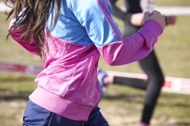 Female athletic runner on a cross country race. Outdoor circuit
