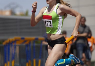Female runner finalizing a relay race in a running track
