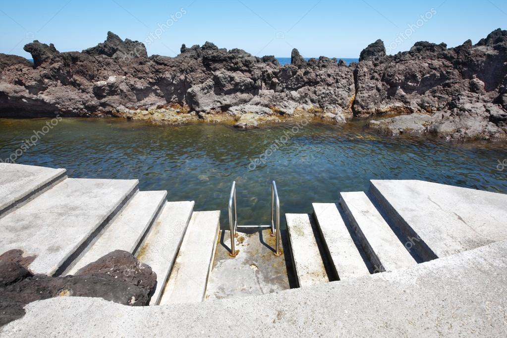 Rotsachtige zwembad strand met trap in biscoitos eiland terceira