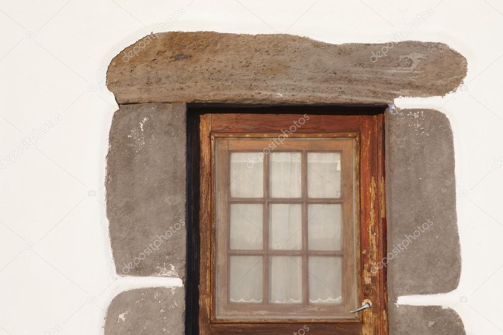 Puerta rústica de madera con marco de piedra sobre una pared blanca ...