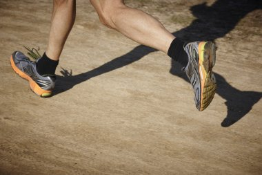 Senior athletic runner legs detail. Outdoor circuit