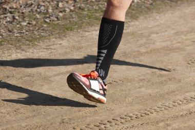 Senior athletic runner leg detail. Outdoor circuit