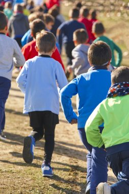 Many athletic children running on a sunny day. Outdoor circuit