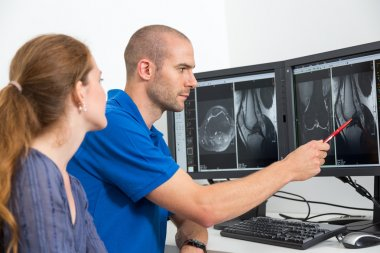 Radiologist councelling a patient using images from tomograpy or MRI