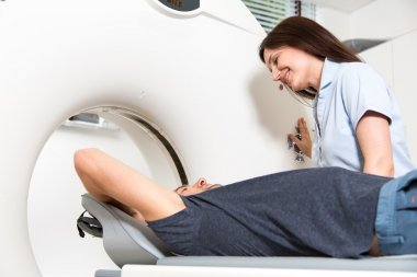 Medical technical assistant preparing scan of the spine with CT