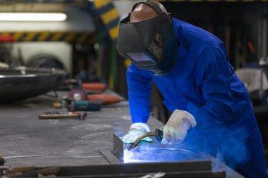 professional welder welding metal pieces in steel construction