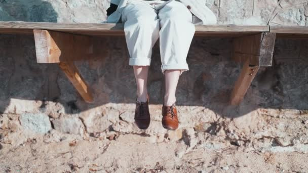 Close-up of female legs in beige trousers brown leather shoes. Elegant outfit. Woman dangles her legs while sitting on the beach. Relaxation and pleasure on a sunny day. Vacation on the coast.