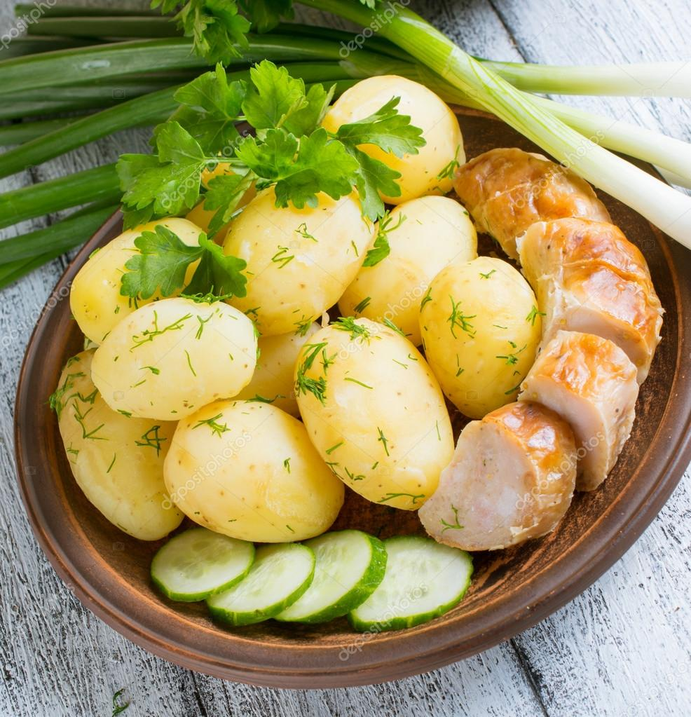 Young boiled potatoes with dill, sausage, cucumber and parsley