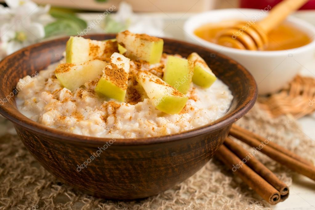 Oatmeal with apple and cinnamon in the bowl, honey and cinnamon