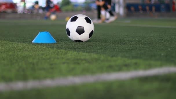 Modrá kuželová značka a fotbalový míč pohybující se na zelené umělé trávníku s rozmazané dítě fotbalový tým trénink na fotbalové akademii.