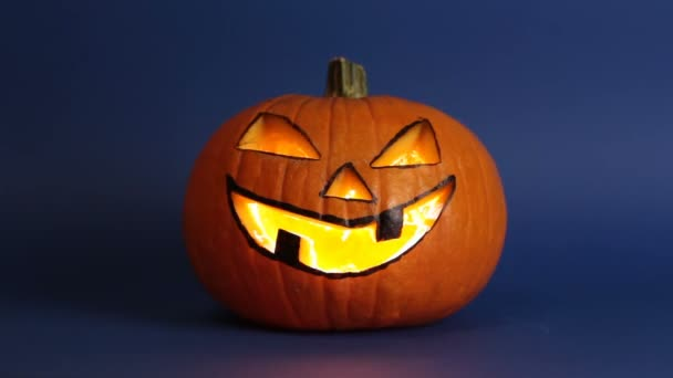 Halloween pumpkin or jack-o-lantern with glowing eyes on a blue background. jack-o-lantern for a Halloween party stands on a table against a dark background.