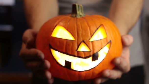 Mladý pán vyrobil lucernu na Halloweenskou párty. Mladý muž, drží v ruce halloween dýni nebo jack-o-lucernu. .